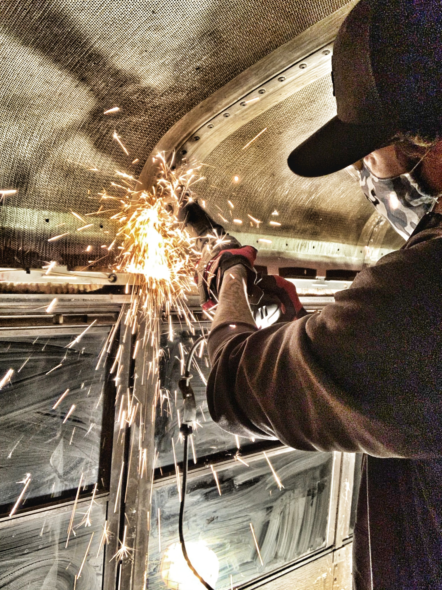 Using the angle grinder to cut grooves into each screw; sparks flying