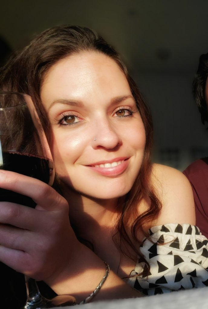 Linds smiling with a glass of wine in hand